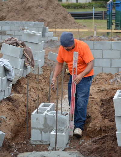 a worker uses a level on a concrete block project
