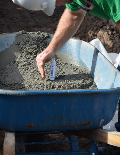 a worker checks cement in a wheelbarrow