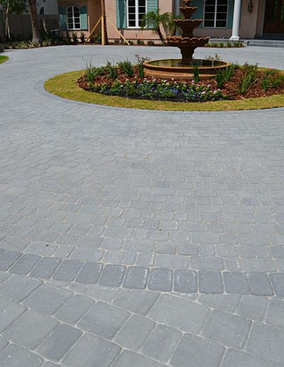a circular driveway surrounds a landscaped island with a fountain