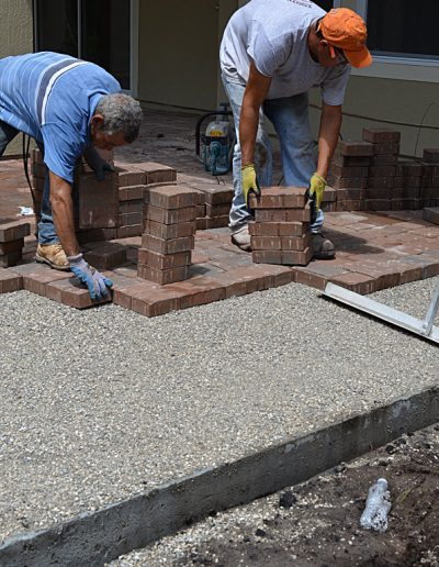 two workers lay pavers in a drive under construction