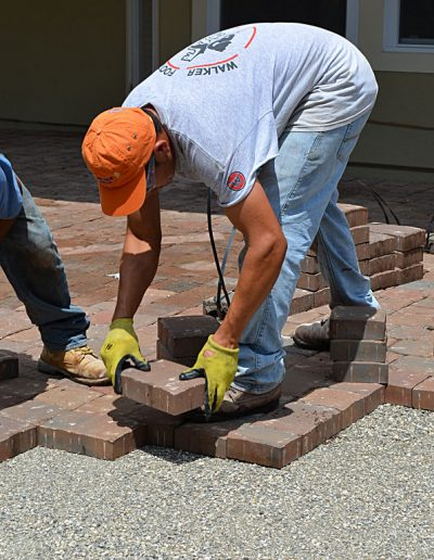 a worker lays pavers in a project