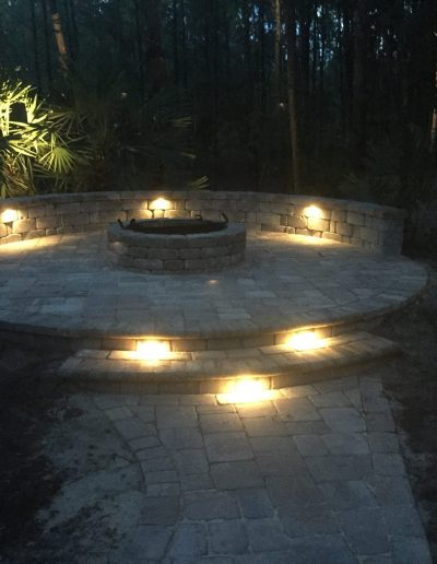 a fire pit built by Walker Footings is lit by recessed lights at night