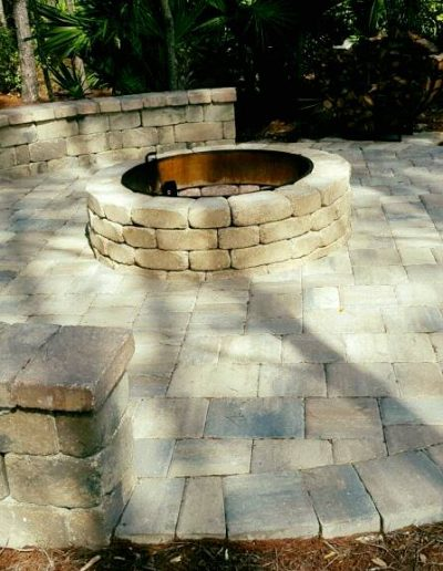 a fire pit built by Walker Footings surrounded on one side by a curved bench