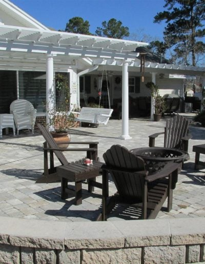 unique patio, covered in part by a pergola, with a seatwall on one side