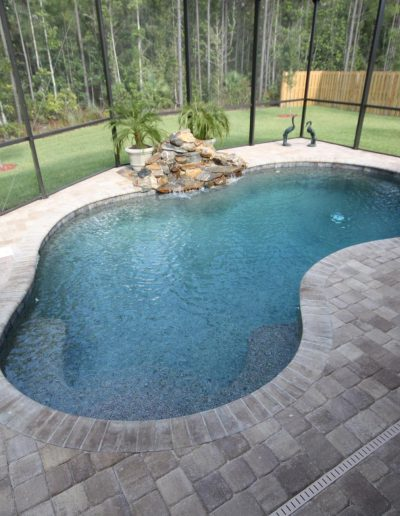 pool deck with a rock waterfall formation