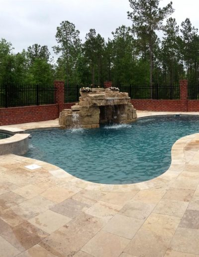 pool deck with a hot tub and rock waterfall feature