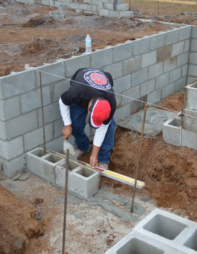 a worker uses a level on a concrete block at a project by Walker Footings