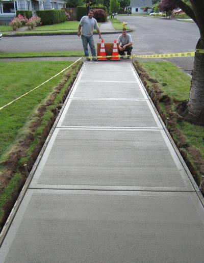 two men look at a freshly poured sidewalk