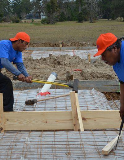 two Walker Footings workers lean in to their work on a concrete footing