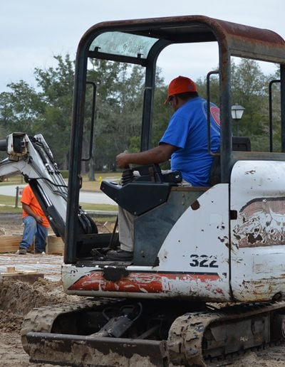 a worker operates a front loader on a job site