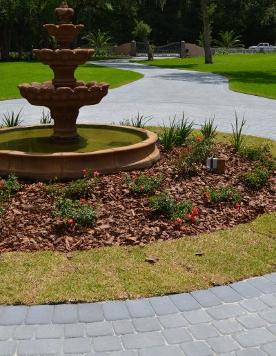 circular driveway around a fountain with landscaping