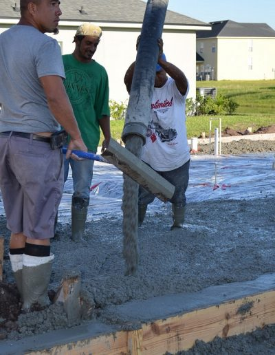 three workers pour concrete at a project