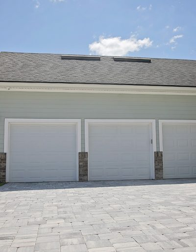 large driveway area outside house with a three car garage