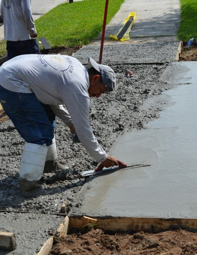 a worker smoothing a newly poured driveway