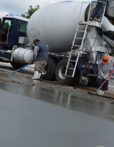a worker smooths out fresh concrete by a cement truck